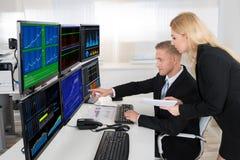 Agentes financieros que supervisan las pantallas de ordenador en oficina fotos de archivo libres de regalías
