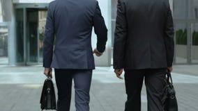 Agentes inmobiliarios que caminan al edificio de oficinas, discutiendo el contrato, sociedad almacen de video