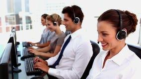 Agentes sonrientes del centro de llamada con las auriculares metrajes