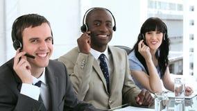 Agentes sonrientes del centro de llamada que trabajan con las auriculares almacen de metraje de vídeo