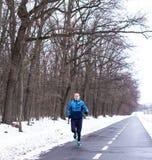 Agentmens in blauwe lopende die slijtage in de wintertijd in werking wordt gesteld royalty-vrije stock fotografie
