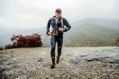 Agentmensen die op middelbare leeftijd in regen op een bergsleep lopen met het lopen van polen stock fotografie