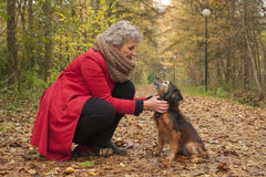 Ager woman and her cute dog in the forest Stock Photo
