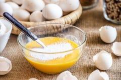 Aggiunga la farina ad una ciotola di vetro con le uova crude immagine stock