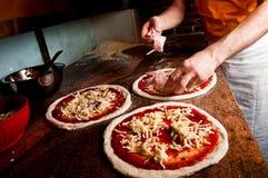 Aggiungendo bacon alla pizza Fotografia Stock