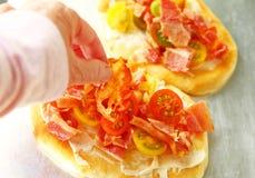 Aggiungendo bacon alle piccole pizze Immagine Stock