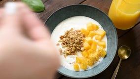 Aggiungendo i semi di chia per fare colazione ciotola del yogurt archivi video