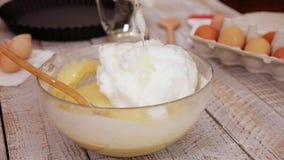 Aggiungendo la frusta del bianco d'uovo agli ingredienti del pan di Spagna stock footage