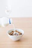 Aggiungendo latte al fiocco di granturco Immagine Stock