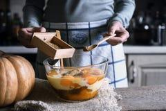 Aggiungendo le spezie nella pasta per lo scarico della zucca agglutinano Immagine Stock