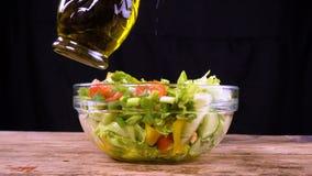 Aggiungendo un olio d'oliva all'insalata in ciotola di vetro archivi video