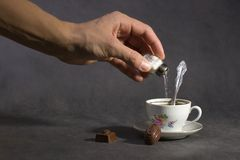 Aggiungendo veleno al caffè Immagine Stock Libera da Diritti