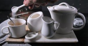 Aggiungendo zucchero ad una tazza calda di cottura a vapore piacevole di tè Immagine Stock Libera da Diritti
