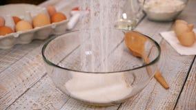 Aggiungendo zucchero ai rossi d'uovo nella ciotola, ingredienti per un pan di Spagna stock footage