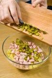 Aggiunta dei cetrioli di marinatura in insalata Fotografie Stock