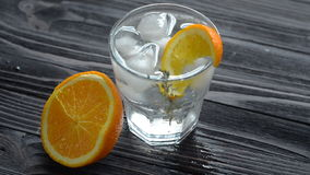 Aggiunta dei cubetti di ghiaccio in vetro con il cocktail fresco video d archivio