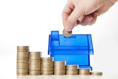 Aggiunta dei soldi nel diagramma della banca piggy e dei soldi della casa Fotografia Stock Libera da Diritti