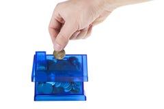 aggiunta dei soldi nella banca blu della casa Fotografia Stock