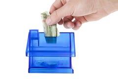 aggiunta dei soldi nella banca blu della casa Immagine Stock
