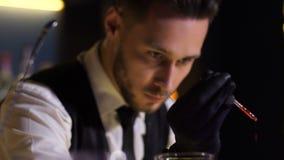Aggiunta del barista amara al cocktail facendo uso del contagoccia stock footage