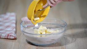 Aggiunta del burro tagliato nella ciotola con farina Punto di produrre la pasta di pasticceria dello shortcrust stock footage