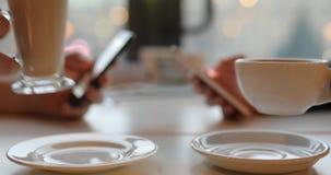Aggiunta del Internet Facendo uso dei telefoni mentre bevendo il primo piano della tazza di caffè archivi video