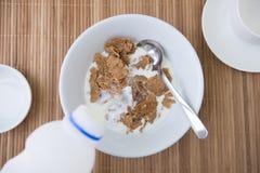 Aggiunta del latte sul fiocco di granturco Immagine Stock Libera da Diritti