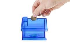 aggiunta della moneta nella banca blu vuota della casa Immagini Stock Libere da Diritti