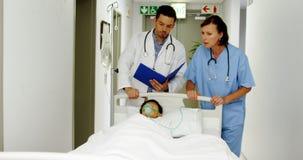 Aggiusta la discussione sopra la perizia medica mentre affrettano un paziente sul pronto soccorso stock footage
