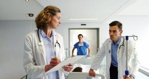 Aggiusta la discussione sopra la perizia medica mentre spingono il letto della barella di emergenza archivi video