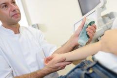 Aggiusti applicarsi lubrificando il gel al braccio paziente del ` s Immagine Stock