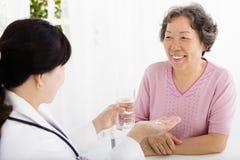 Aggiusti dare il farmaco e l'acqua alla donna senior Immagine Stock Libera da Diritti