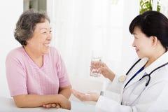Aggiusti dare il farmaco e l'acqua alla donna senior Immagine Stock