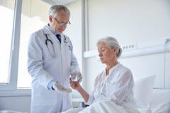 Aggiusti dare la medicina alla donna senior all'ospedale Fotografia Stock