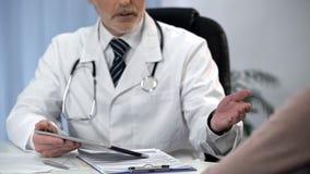 Aggiusti dire la diagnosi al paziente, discutente i benefici del trattamento chirurgico immagine stock