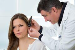Aggiusti ENT che controlla l'orecchio con l'otoscopio al paziente della donna Fotografia Stock