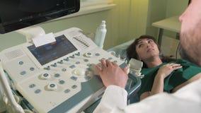 Aggiusti fare l'ultrasuono 3d sulla pancia della donna di t in clinica 4k video d archivio