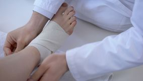 Aggiusti il bendaggio della caviglia storta, lesione corrente dopo l'allenamento, primo piano della gamba stock footage