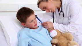 Aggiusti il controllo delle orecchie di piccolo ragazzo malato che si siede a letto stock footage