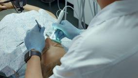 Aggiusti il dentista che utilizza il microscopio dentario nell'ufficio dentario per l'operazione di un paziente della donna archivi video