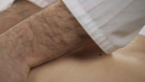 Aggiusti il massaggiatore che segna la parte posteriore paziente del ` s stock footage