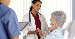 Aggiusti il paziente anziano di consolazione della donna nel letto di ospedale fotografie stock