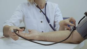 Aggiusti il polso arterioso del controllo dell'uomo senior con il tonometer e lo stetoscopio stock footage