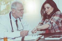 Aggiusti il polso d'esame di un paziente femminile, effetto della luce immagine stock libera da diritti