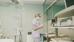 Aggiusti il vestiario di protezione d'uso che esegue la chirurgia facendo uso dell'attrezzatura sterilizzata archivi video