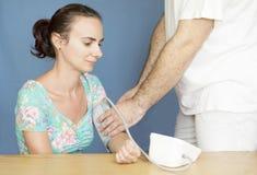 Aggiusti l'aiuto della donna misurare la sua pressione sanguigna Immagini Stock