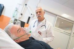 Aggiusti l'esame del paziente maschio senior che inala attraverso la maschera di ossigeno fotografia stock libera da diritti