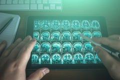 Aggiusti l'esame della compressa sulla sua tavola con la scansione del cervello di RMI o i raggi x, concetto diagnostico medico m fotografie stock libere da diritti