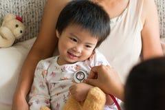 Aggiusti l'esame della ragazza del bambino in un ospedale con la sua mamma immagine stock libera da diritti
