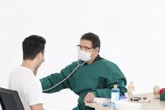 Aggiusti l'esame paziente dell'uomo con l'uomo su fondo bianco fotografia stock